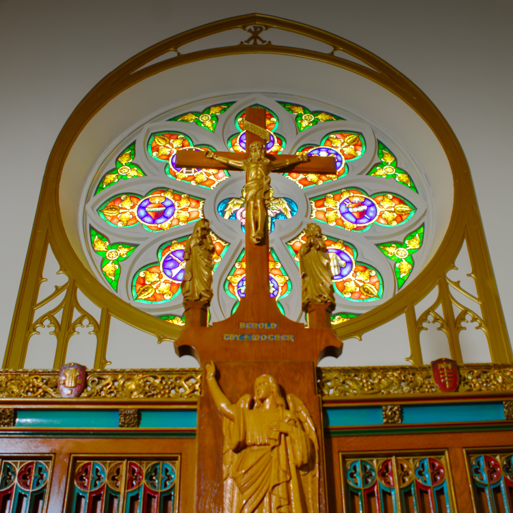 Wooden Crucifix with Rose window in the background